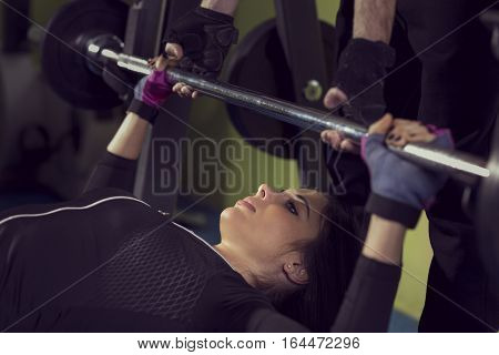 Attractive muscular young woman working out in a gym lying on a bench lifting weights while her instructor is supervising her efforts