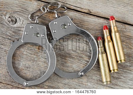 Dummy cartridges and handcuffs on the wooden background
