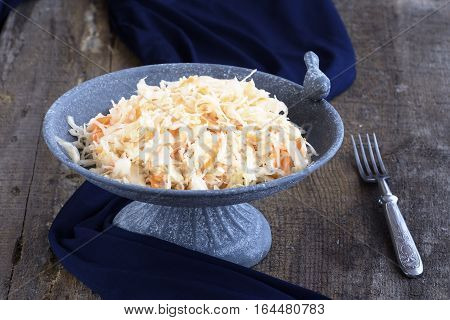 Homemade Sauerkraut with carrots in an elegant stone plate with a bird on a rough wooden background with dark blue cloth and fork.