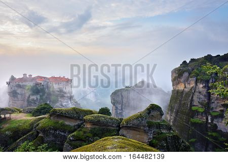 Meteora monasteries. Beautiful view on the Holy Monastery of Varlaam placed on the edge of high rock covered of the morning clouds and mist at sunrise Kastraki Greece