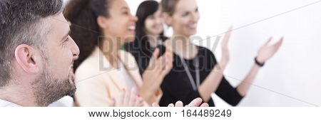 Elegant man and women clapping hands and smiling after company presentation