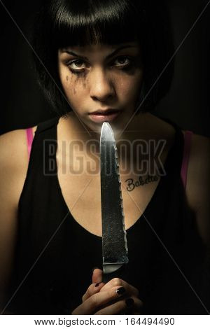 Young crying woman killer. Knife murder suicide. Crazy girl. A young girl with problems is holding a big knife and points it in her mouth. Suicide, psychopathology murder concept. Black background.