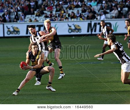 MELBOURNE - AUGUST 15: Richmond's Brett Deledio dodges Collingwood players - Collingwood vs Richmond, August 15, 2009 in Melbourne, Australia.