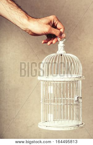Hand holding an empty cage. Absence of ideas and dreams. Freedom and hope. Hand holding an empty cage. Absence of ideas and dreams. Freedom and hope. Solitude and loneliness concept. The arm of a man holding a white cage with nothing inside. Freedom of ex