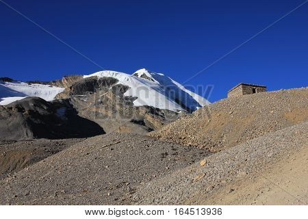 Moraine and peak covered by glacier. Scenery just before the Thorung La mountain pass Annapurna Conservation Area. Shelter.