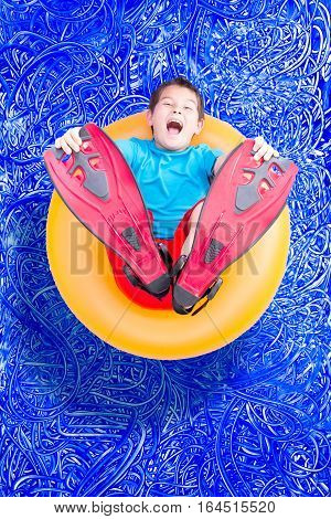 Young Boy In Flippers Playing In A Pool