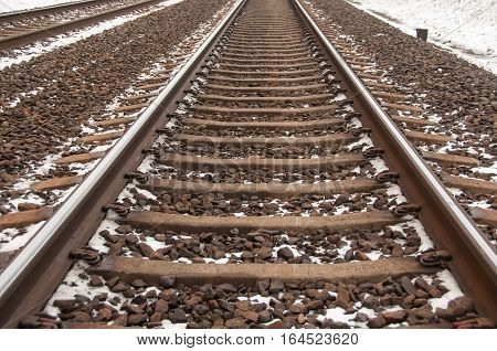 Straight railway. Railroad covered with snow. Metal construction.