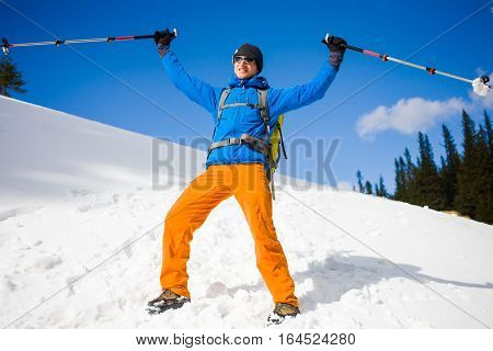 Man With Trekking Poles Goes Through The Snow In The Mountains.