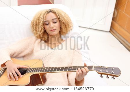 Playing the guitar. Guitar lessons. Acoustic guitar. Relax while playing the guitar. Girl playing the guitar.