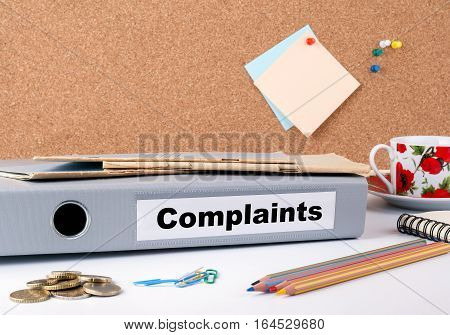 Complaints.Folder on office desk. Money, Coffee Mug and colored pencils.