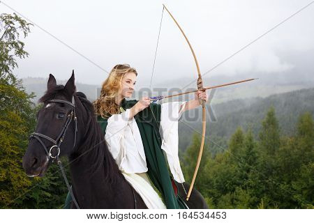 Young horseback girl in white dress shooting arrow from bow in mountain forest. Historical equine background