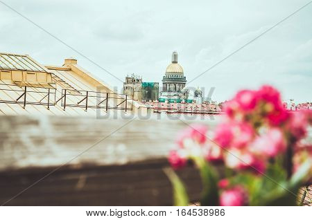 SAINT-PETERSBURG RUSSIA - august 2016: Scenic view on famous historical golden dome of Saint Isaac's Cathedral and old city from roof. Summer cityscape over the rooftops. Editorial use only.