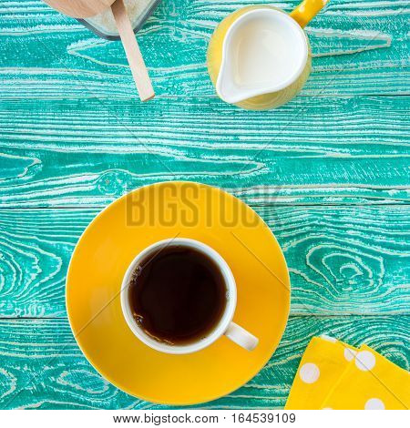 cup of black tea on yellow plate and yellow milk jug and sugar-bowl on turquoise colored old wooden table with yellow napkin at polka dots top view