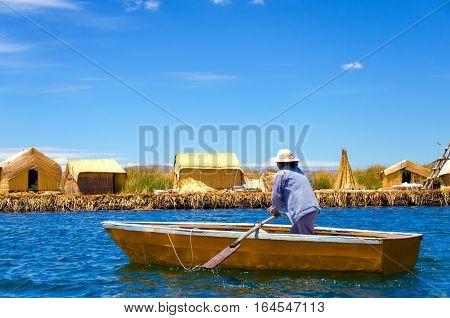 UROS FLOATING ISLANDS PERU - SEPTEMBER 19: Woman in a small boat in the Uros Floating Islands Peru on September 19 2014