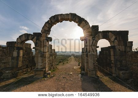 The Tingis Gate, looking back down the Decumanus Maximus in Volubilis on sunny day with few clouds, Morocco.