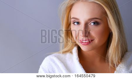 Smiling woman in white bathrobe, isolated on gray background.