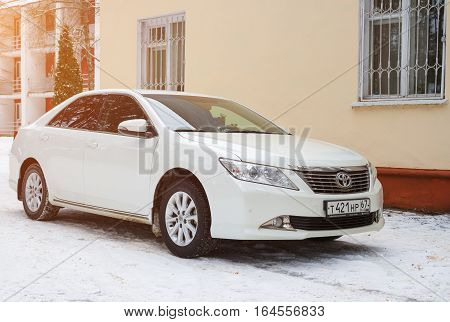 Smolensk, Russia - December 16, 2016: New luxury Toyota Camry parked near the house at winter evening.