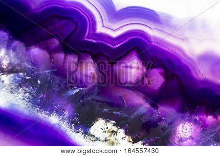 A colorful macro photo of a purple agate stone.