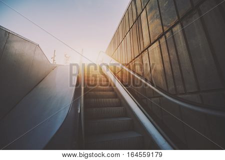 Outdoor city escalator stairway under evening sun with tiled rusty concrete wall on the right wide view from bottom rubber rail vintage color filter