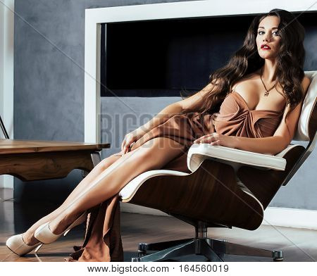 beauty yong brunette woman sitting near fireplace at home, lifestyle people concept close up