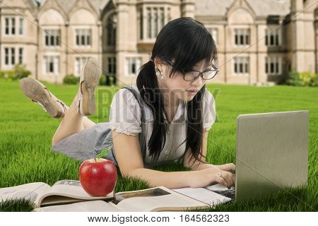 Photo of Asian high school student studying with book while lying and using laptop computer at the park