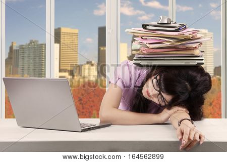 Photo of young entrepreneur taking rest with a stack of documents over her head in the office