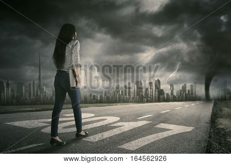 Rear view of young businesswoman walking on the road while carrying a laptop with number 2017 and hurricane