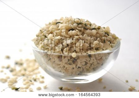 Crushed Hemp hearts or seeds - natural and nutritious dietary supplement suitable for vegans, vegetarians, raw foodists and allergy sufferers, in a glass bowl, closeup on white background