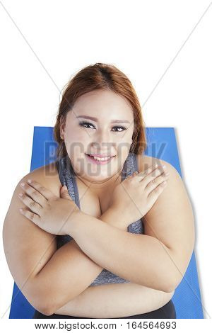 Unique perspective overweight young woman doing crunches on the mattress isolated on white background