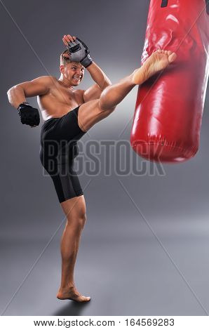 Muscular Fighter Practicing Some Kicks With Punching Bag In Black Boxing Gloves. Boxing On Gray Back