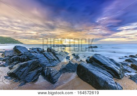 Dawn on the beach with brightly colored clouds, beneath a rock with beautiful shapes create beautiful scenery welcome bright day fresh