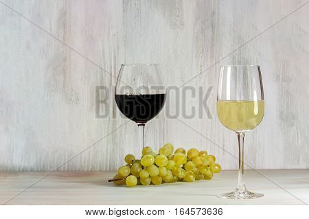 Two glasses of wine, white and red in the background, with a bunch of grapes, on a wooden texture with copy space