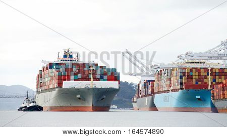 Oakland CA - January 02 2017: Tugboats PACIFIC STAR and LYNN MARIE assist COSCO JAPAN to maneuver into the Port of Oakland
