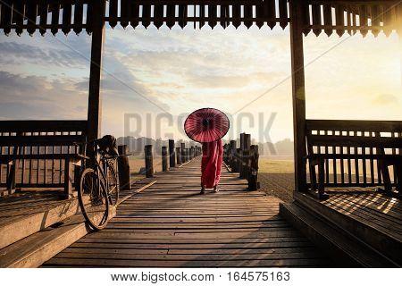 Monk walk on the wooded bridge U Bein Bridge Mandalay Myanmar