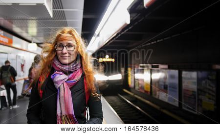 Beautiful young woman waiting subway at underground - train arrives, wide angle