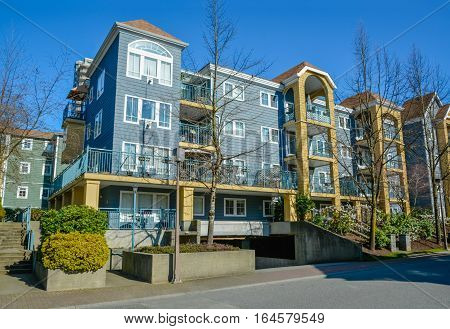 Low rise residential building on a street with blue sky background. Vancouver on winter season