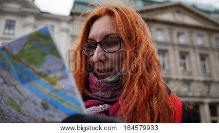 Yong tourist - woman with red hair and glasses looking map in Vienna, close up