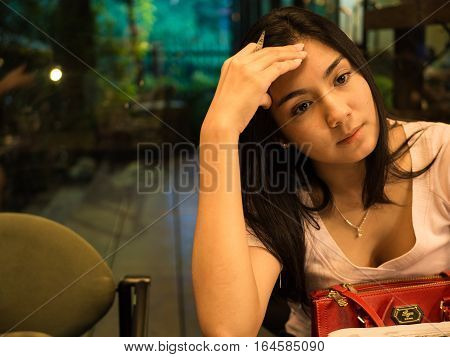 Asian woman sitting on the chair and thinking something