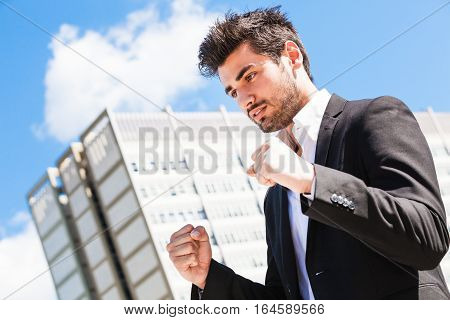Career of young worker man. Business man. A young businessman with hands closed in a fist. Behind him, an office building and blue sky.