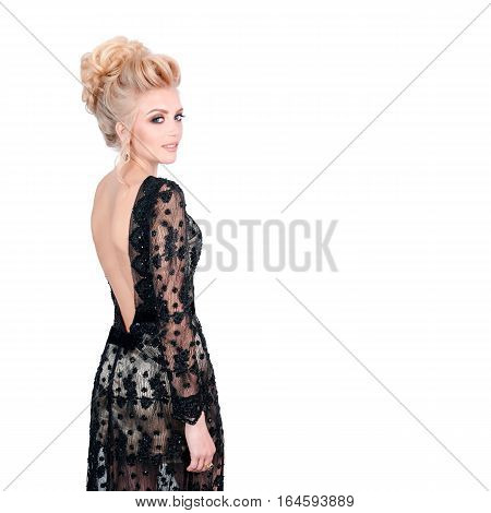 Beautiful blonde woman in elegant black evening dress with updo hairstyle. Lady looking over her shoulder on white background. Free space for text. Fashion photo for advertising something
