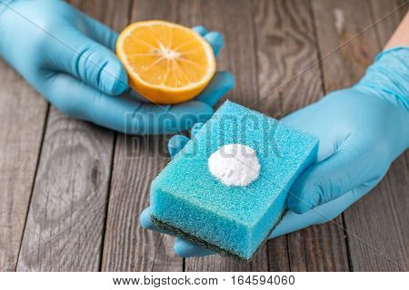 Eco-friendly natural cleaners lemon baking soda and cloth on wooden table in hand on wooden table