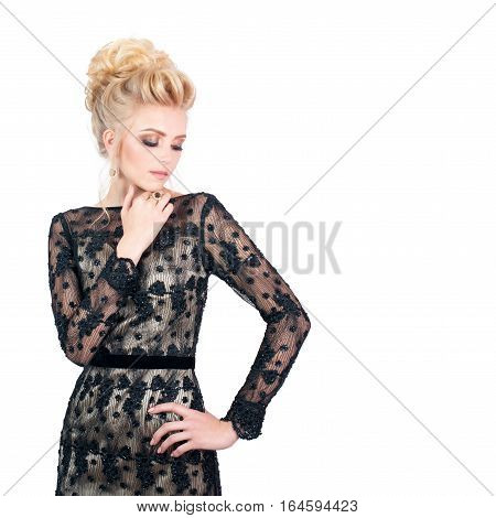 Beautiful blonde woman in elegant black evening dress with updo hairstyle. Her eyes is closed showing bright makeup. Free space for text. Fashion photo for advertising something.