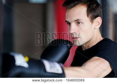 Portrait of young boxer training in gym