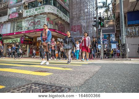 Hong Kong, China - December 6, 2016: asian women crossing Yee Wo Street famous for Sasa shopping center on Hennessy Road. Causaway Bay is a one stop shop for fashion, luxury, and urban stores.