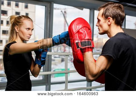 Training young sportswoman with coach in boxing gloves in gym