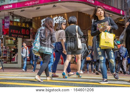 Hong Kong, China - December 6, 2016: asian people cross Yee Wo Street junction with Hennessy Road, Causaway Bay, the luxury shopping district, one of the busiest junctions in Hong Kong.