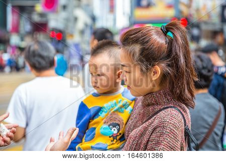 Hong Kong, China - December 6, 2016: Potrait of a mother and a son at the Yee Wo Street junction on Hennessy road downtown of Causaway Bay, one of the best travel destinations for tourists.