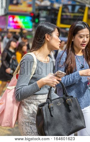 Hong Kong, China - December 6, 2016: portrait of two Asian women with branded bags and smart phones in Yee Wo Street junction with Hennessy Road, Causaway Bay, the luxury shopping district, Hong Kong.