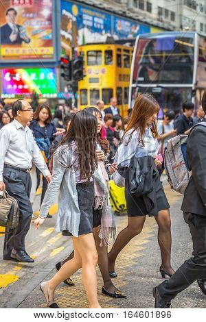 Hong Kong, China - December 6, 2016: Three young and asian business women at bay Causway crosswalk on Hennessy Road, Causaway Bay one of the busiest junctions in Hong Kong.
