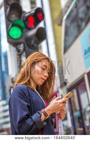 Hong Kong, China - December 6, 2016: A busy woman at the traffic signal of Yee Wo street junction, located at Causaway Bay on the Hennessy Road. This busy junction is famous for fashion and luxury.